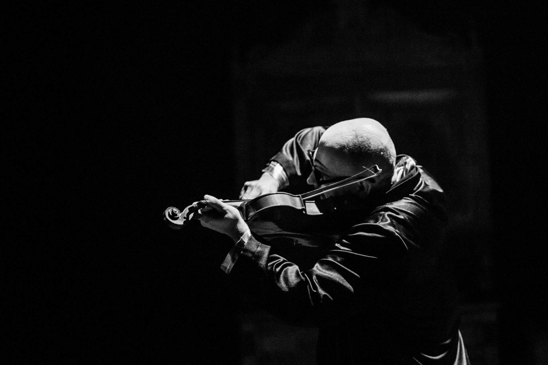 czarno białe zdjęcie ze spektaklu Rzeźnia. Na środku w ciemności widać postać mężczyzny grającego na skrzypcach.