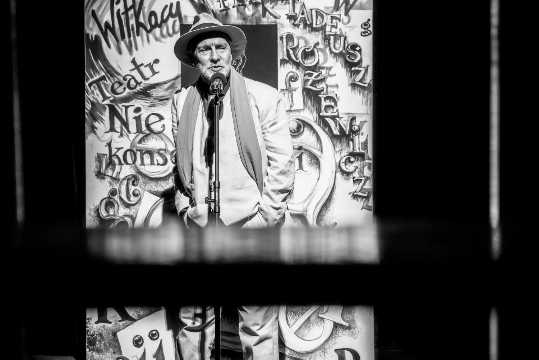 Czarno białe zdjęcie ze spektaklu Akt Prerywany. Mężczyzna w garniturze i kapeluszu mówi do mikrofonu na statywie. Za nim ściana pokryta napisami związanymi z tytułem spektaklu