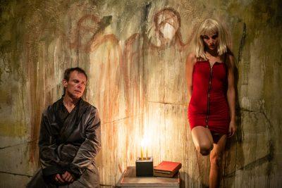 zdjęcie ze spektaklu The Underground Man. Po lewej siedzi mężczyzna w starym szlafroku, po prawej stoi młoda blondynka w wyzywającej czerwonej sukience. Między nimi stoi stolik, na którym jest książka i zapalona świeca.