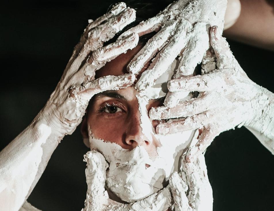 """zdjęcie ze spektaklu """"Hic sunt dracones"""". W centrum kobieca twarz pokryta jasną gliną - widać tylko jedno oko. Na twarz nakładaja się posmarowane gliną 4 dłonie"""